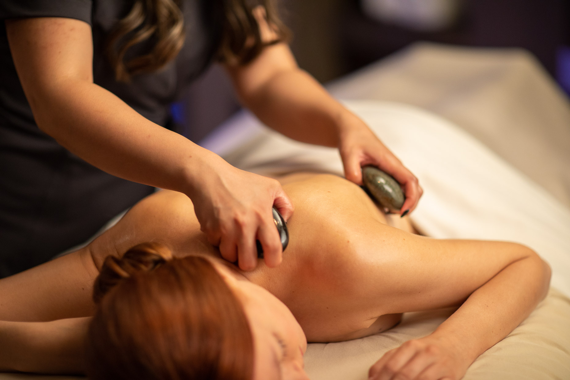 Woman enjoys a stone massage in a spa
