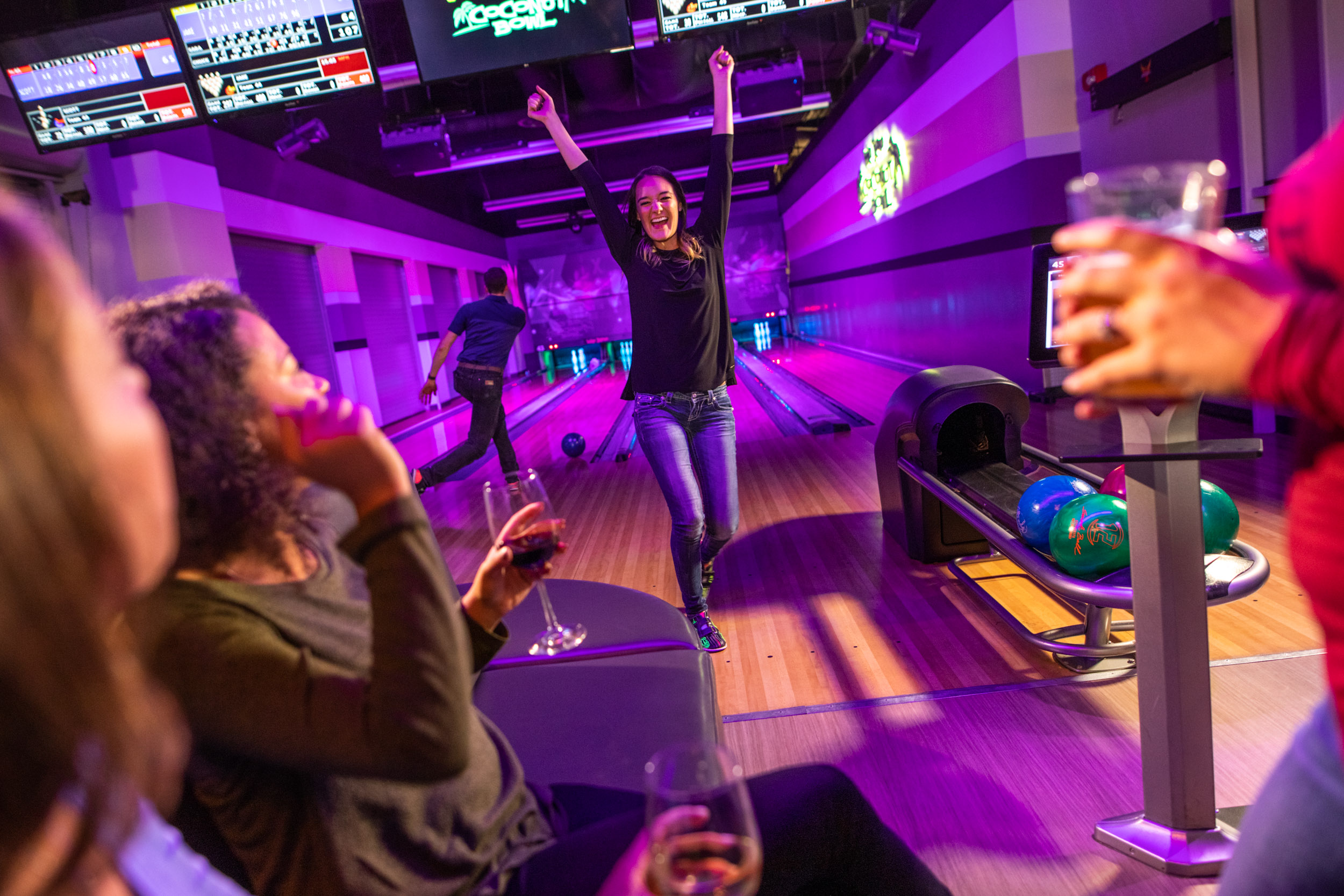 Woman celebrate at black light bowling.