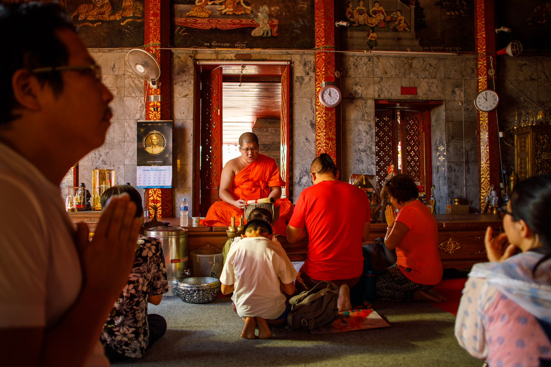 Buddhist monk blesses people during prayer