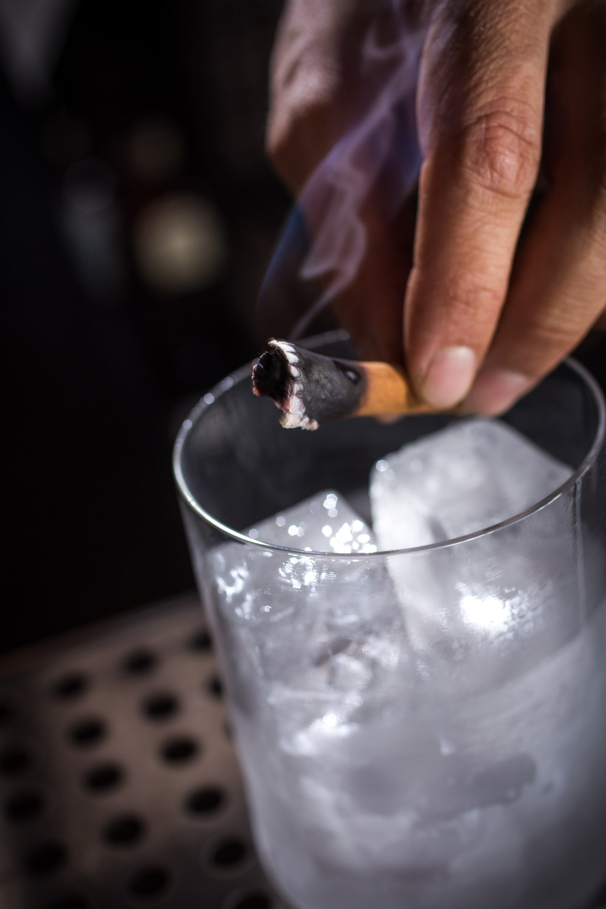 Bartender add burning cinnamon to a cocktail