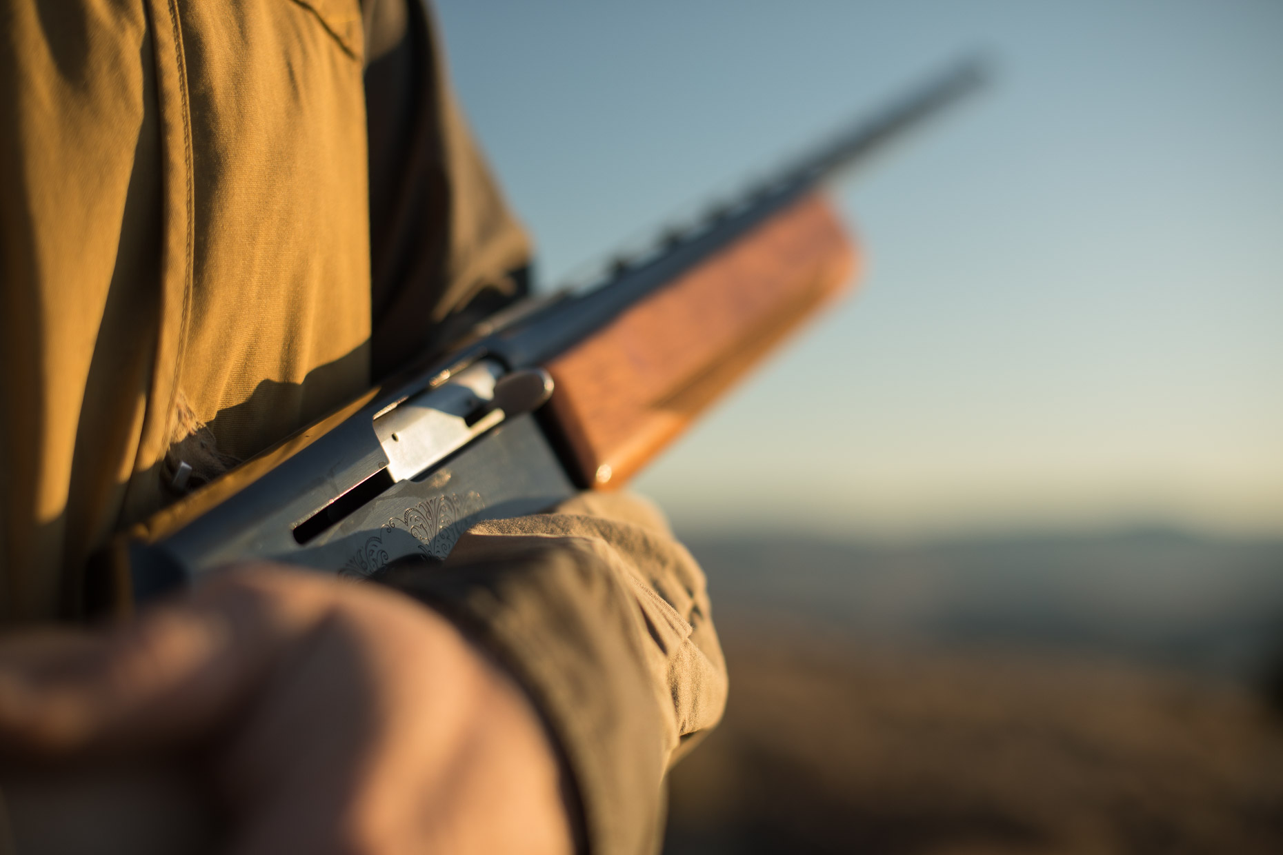 Man holds his shotgun during a chukar hunt