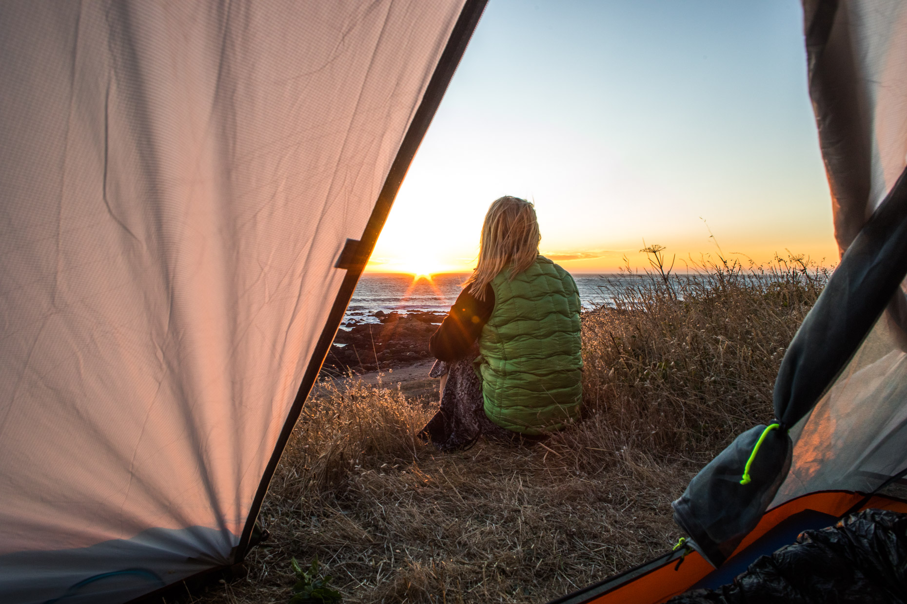 Woman watches the sunset from her tent on The Lost Coast Trail
