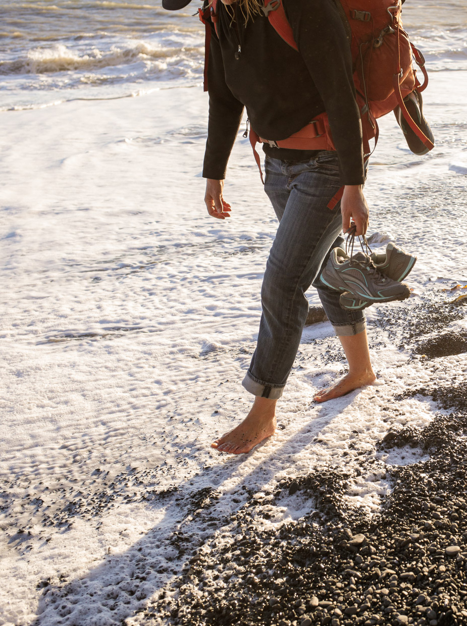 Women walks barefoot on the beach on the Lost Coast Trail in Northern California