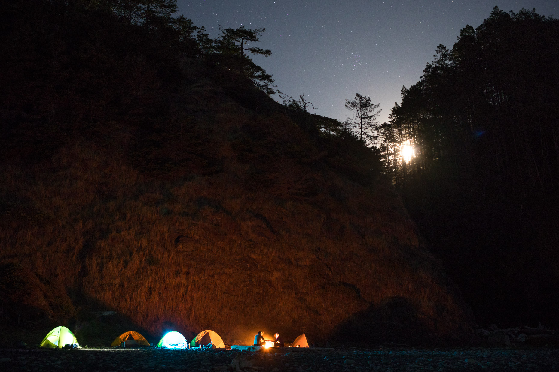 Fire illuminates the backpackers campsite