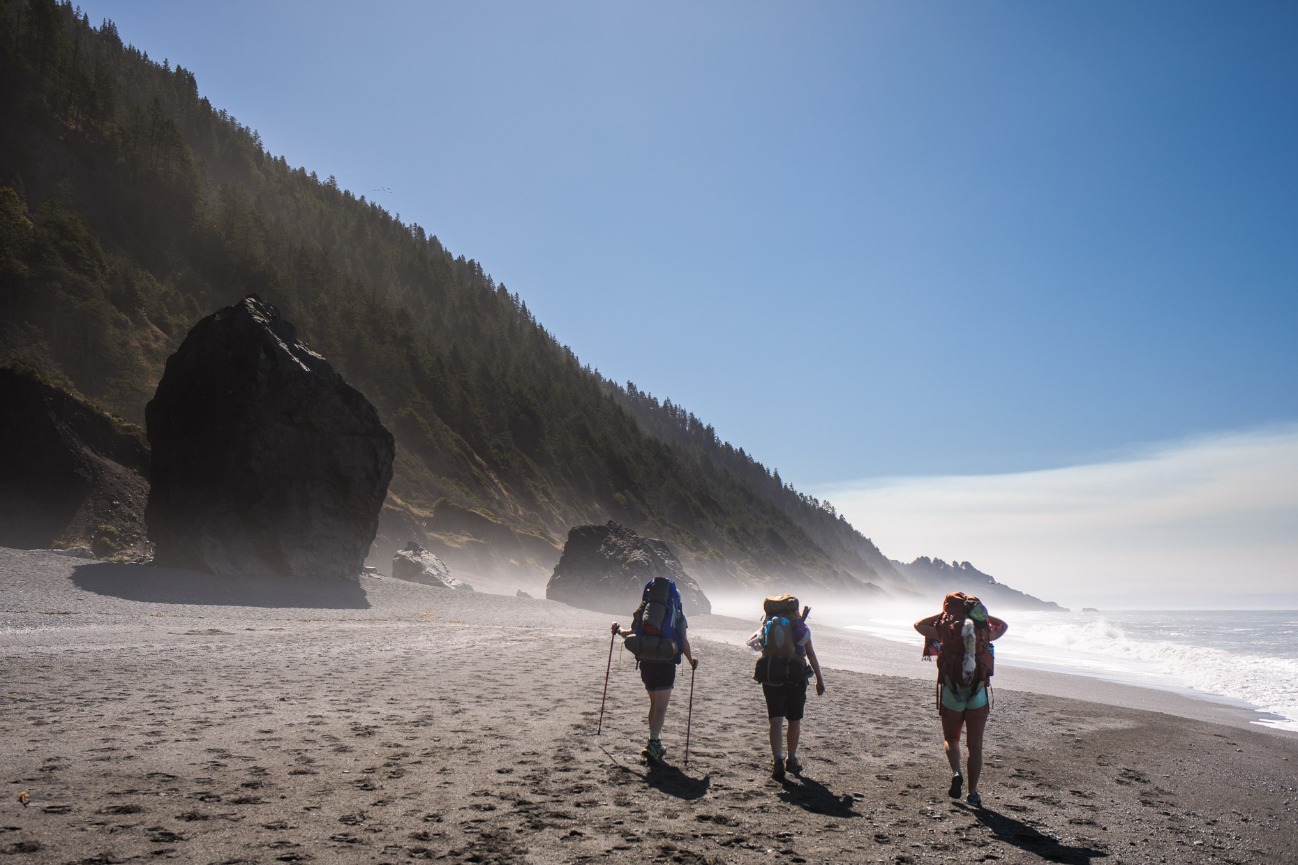 backpackers hike past ocean boulders on the lost coast trail