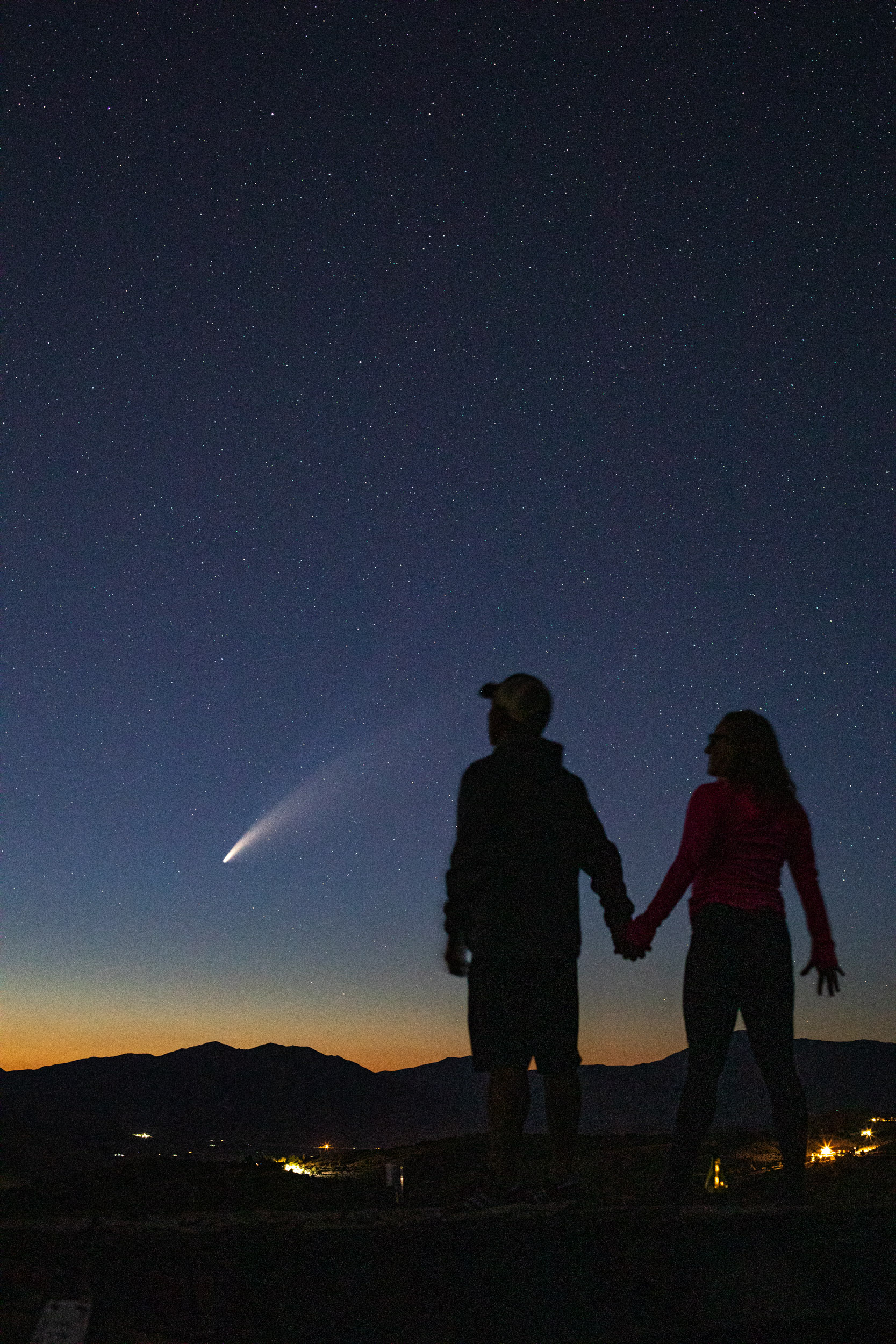 couple hold hands while viewing comet NeoWise