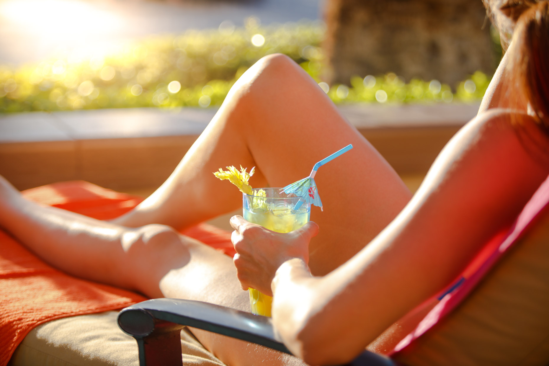 A woman lounges pool side in the sun with a cocktail