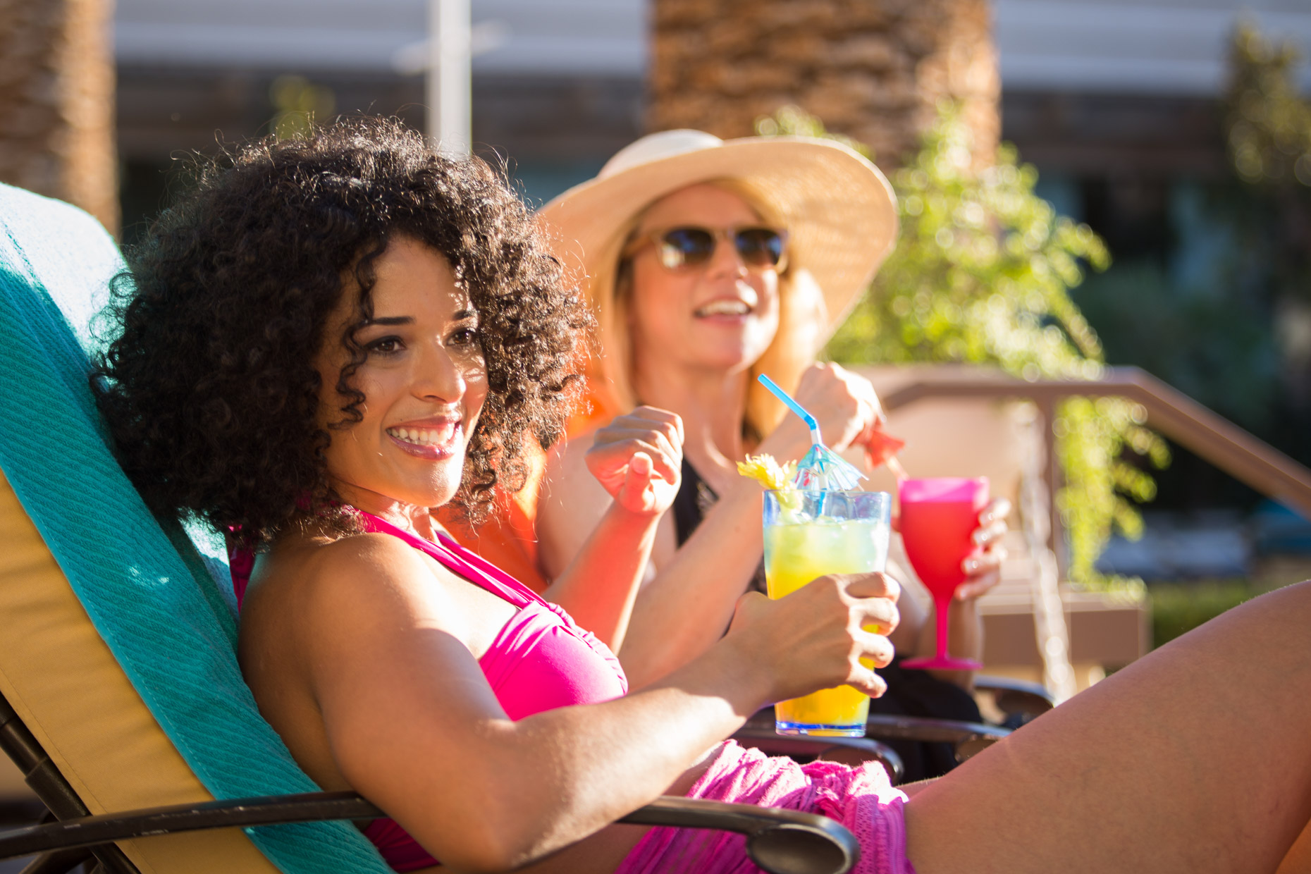 Women enjoy a poolside cocktail