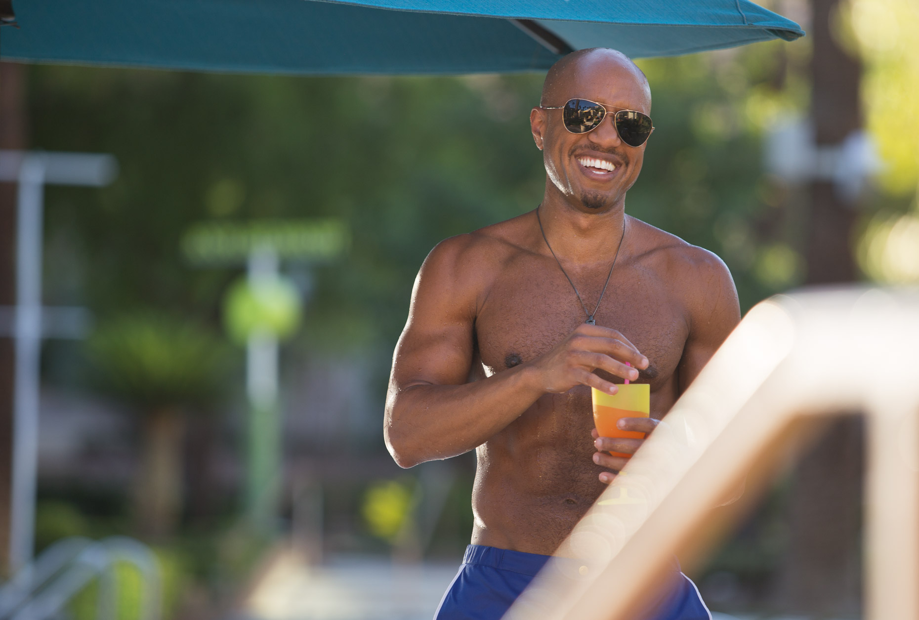 Well fit man enjoys a poolside cocktail