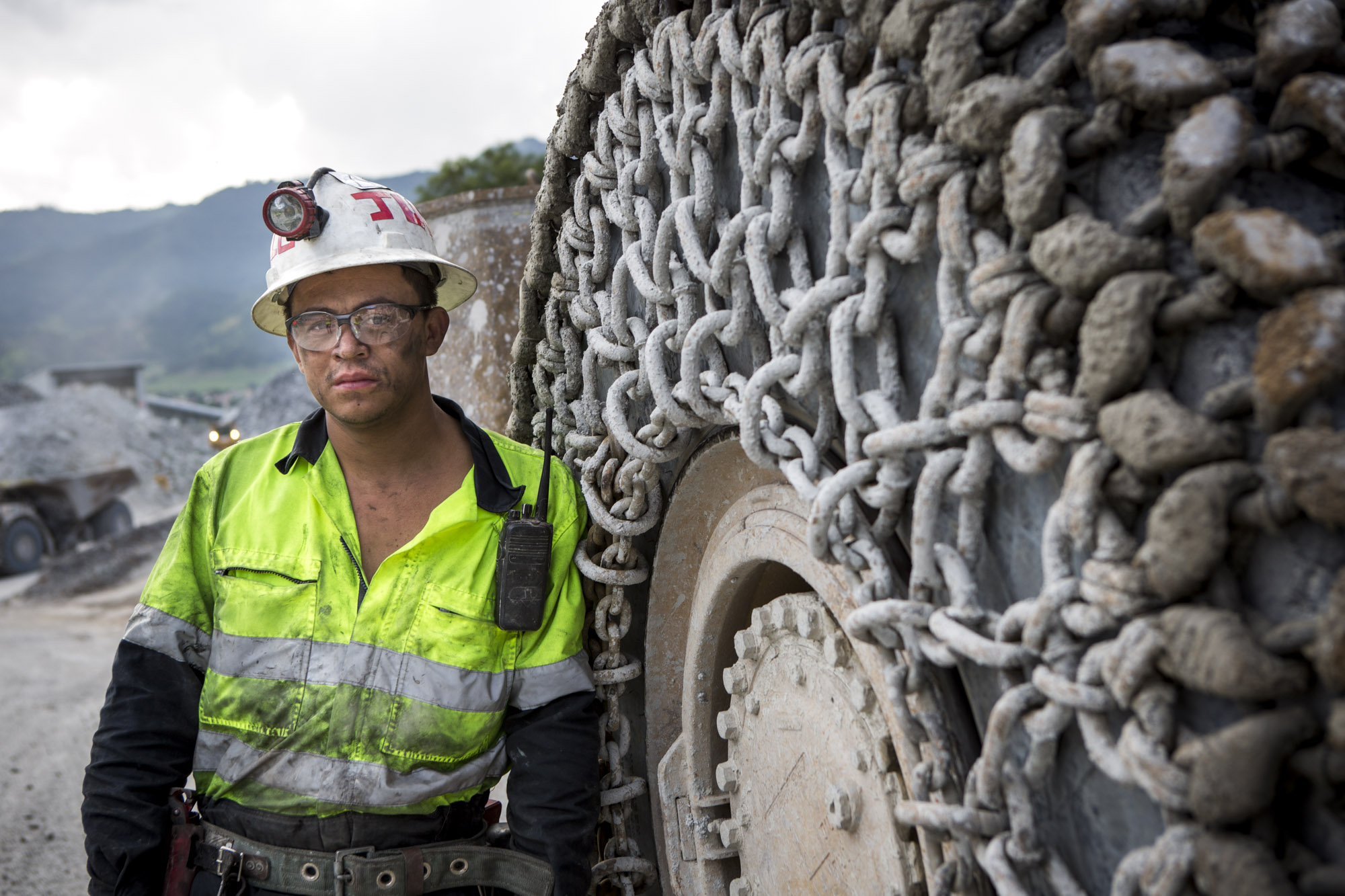 Miner stands near a massive mining tire
