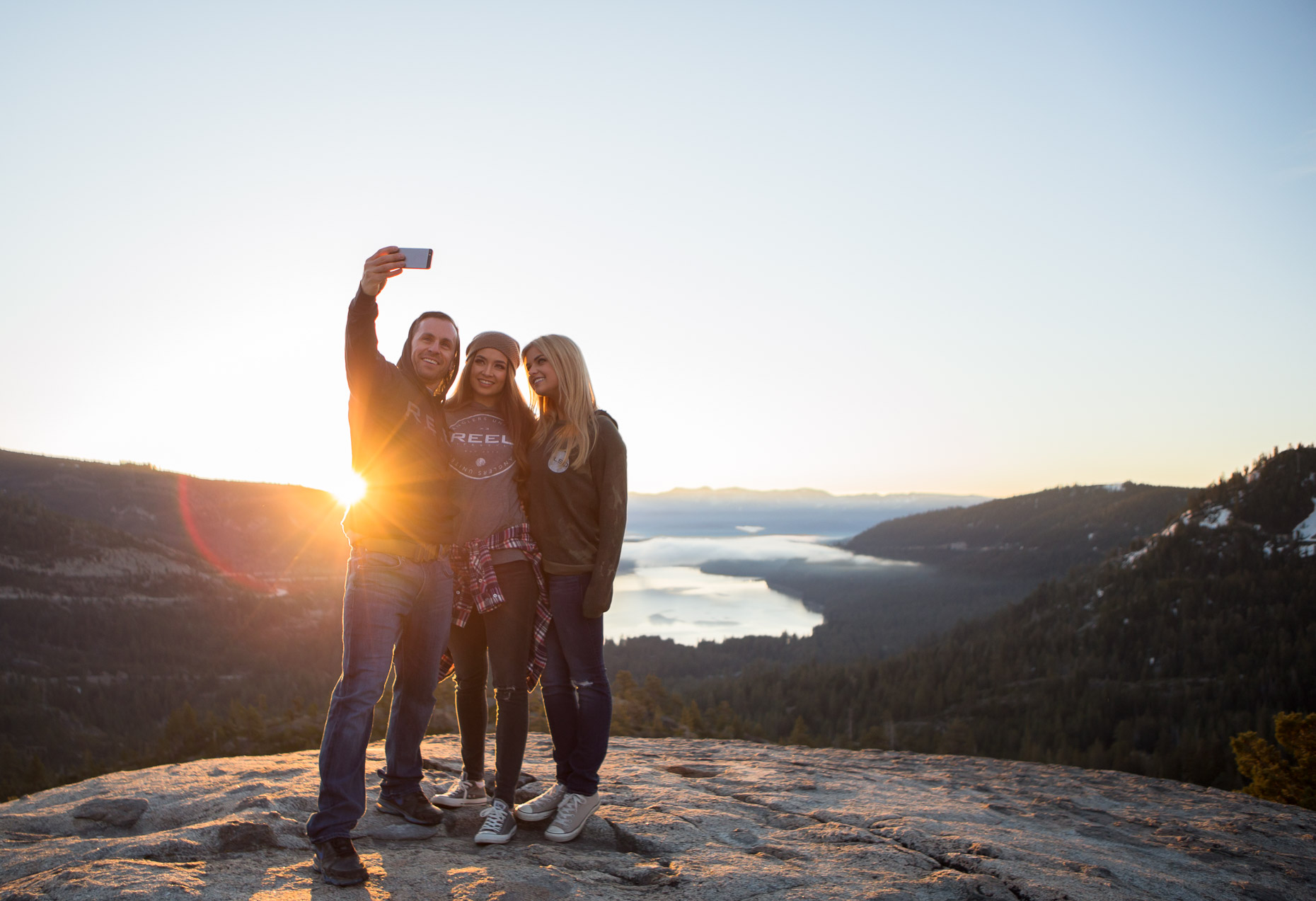 three people take a selfie during  the sun rise above a mountain lake