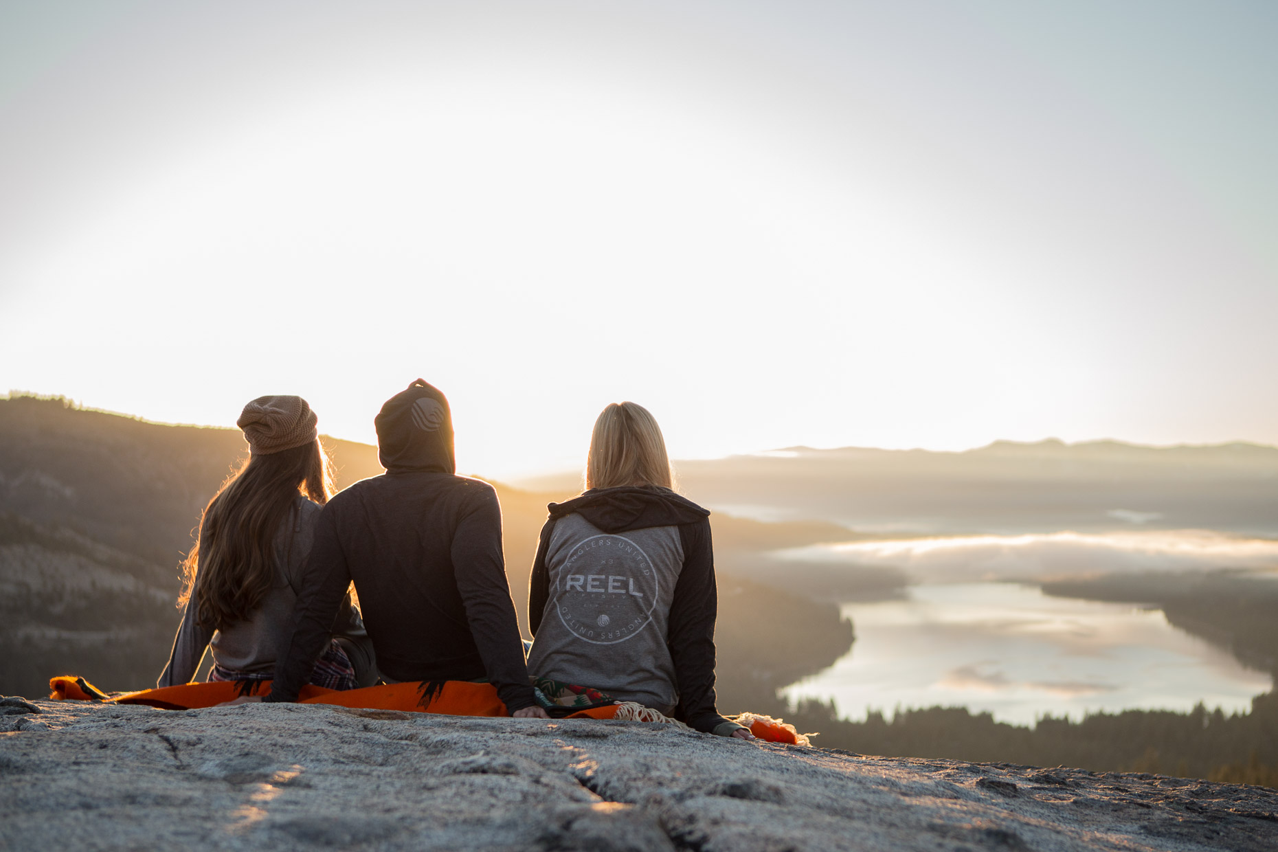 three people watch the sun rise above a mountain lake