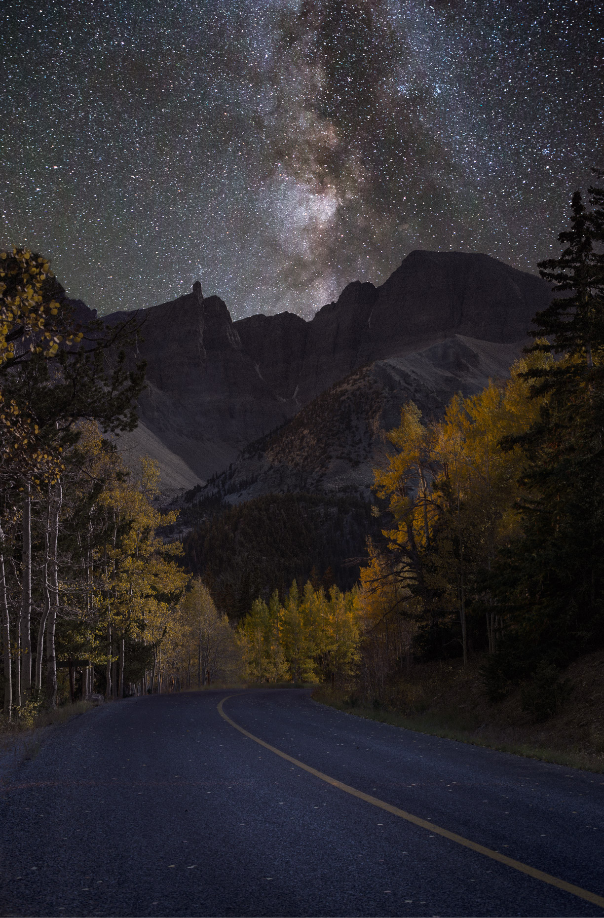 two lane road and Milky Way in the sky with autumn colors