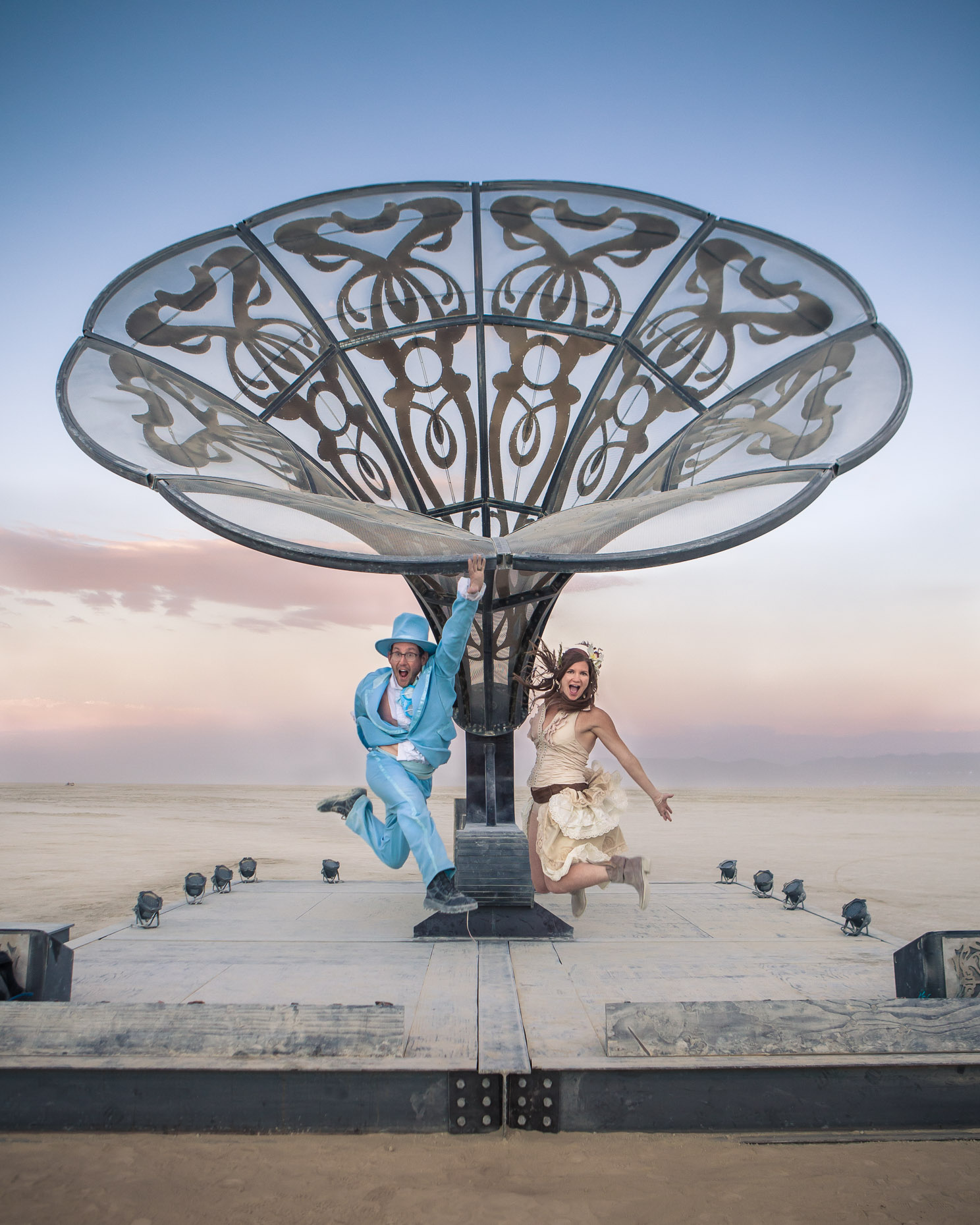 Couple jump in front of art sculpture at Burning Man