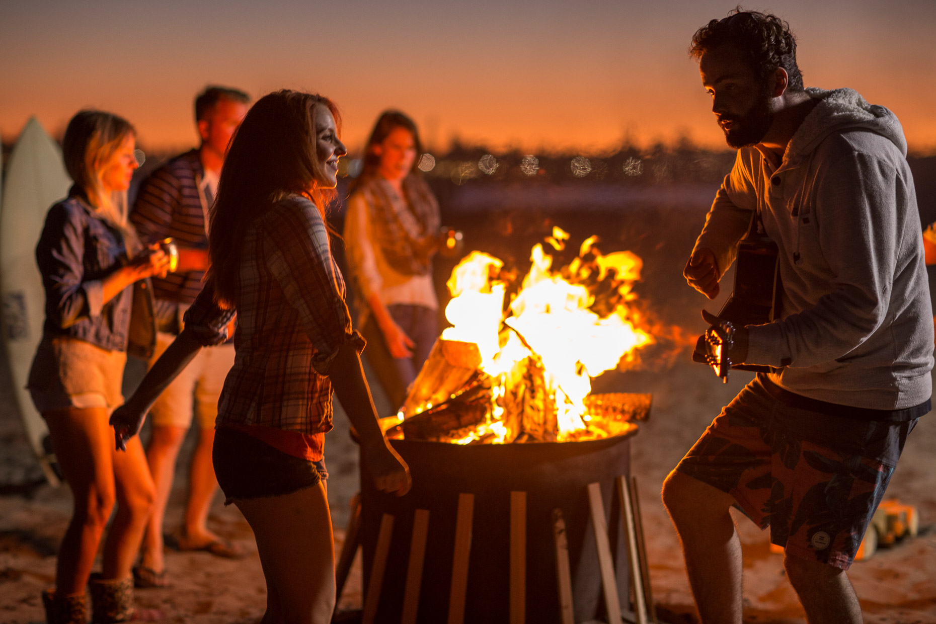 Friends enjoy a fire and music on the beach