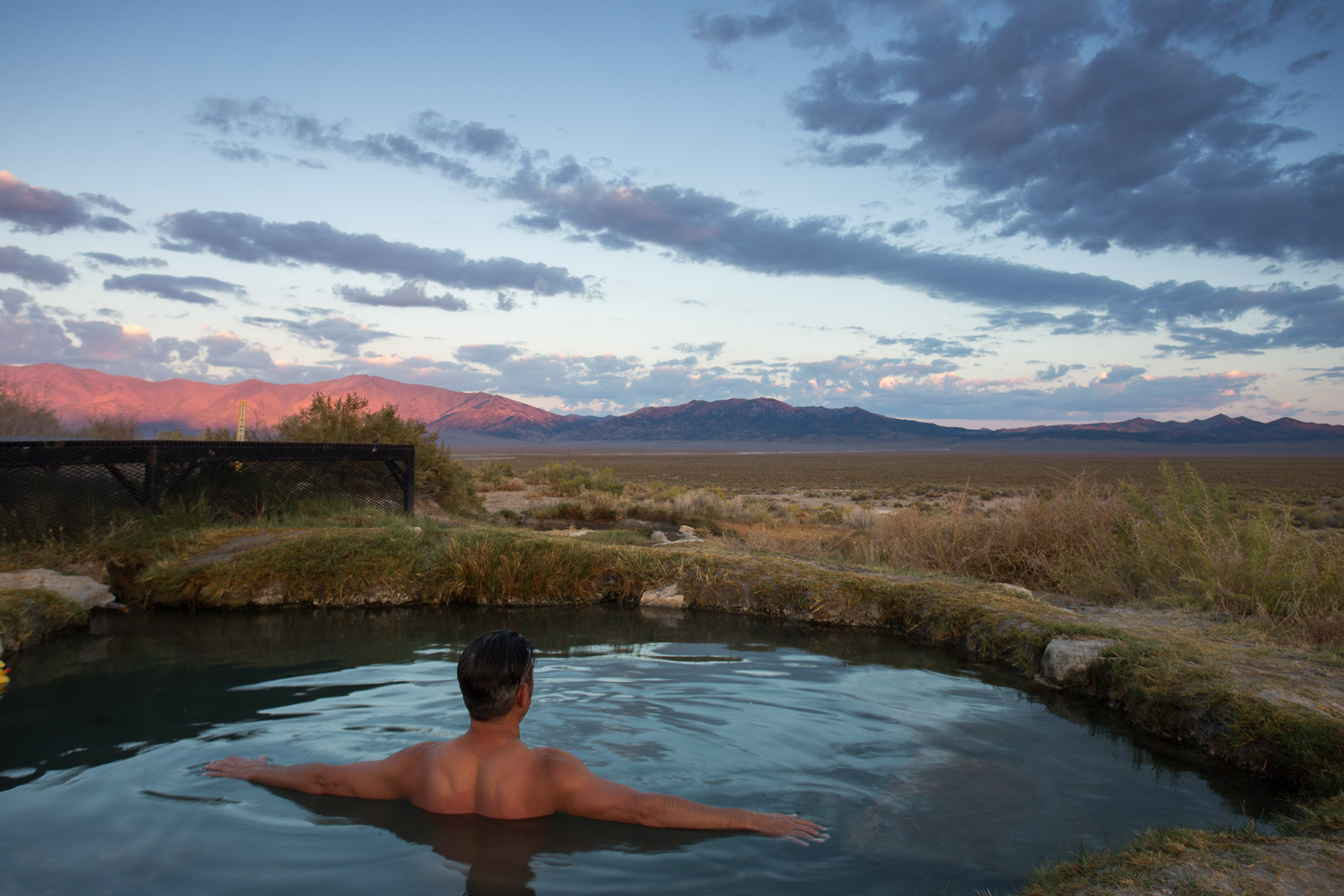 Man in hot springs at sunrise