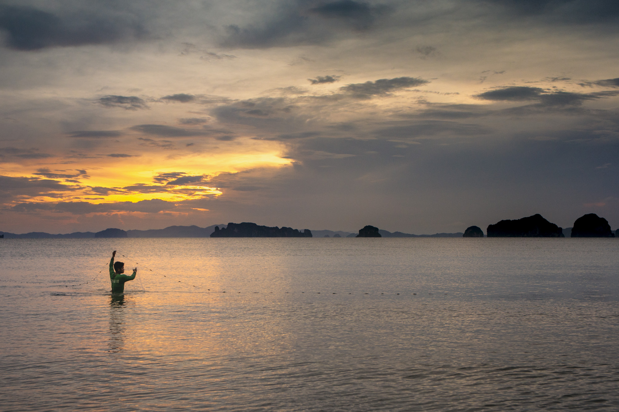 Fisherman cast a hand net in southern Thailand