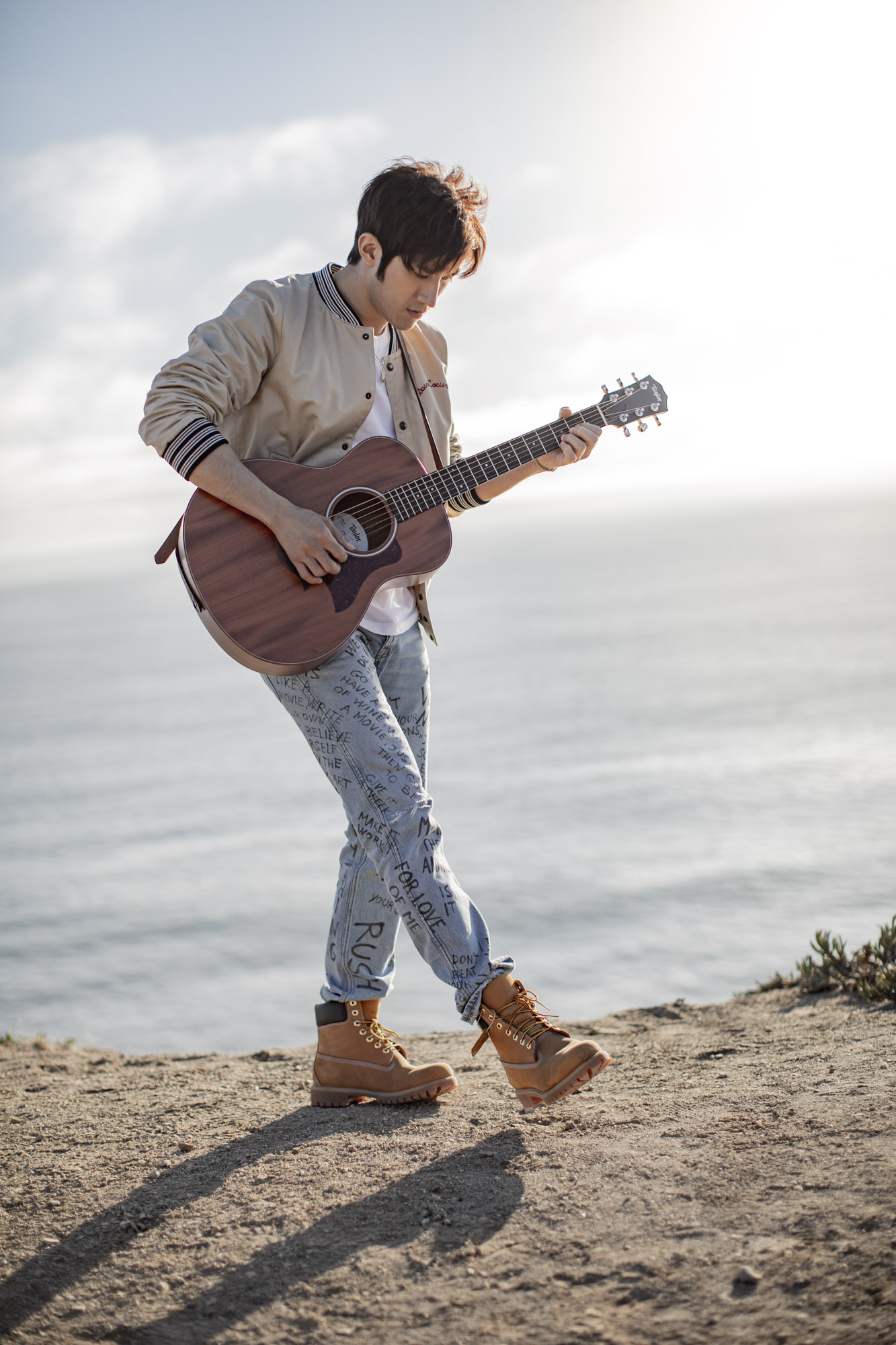 Man plays a guitar with the Pacific Ocean in the background