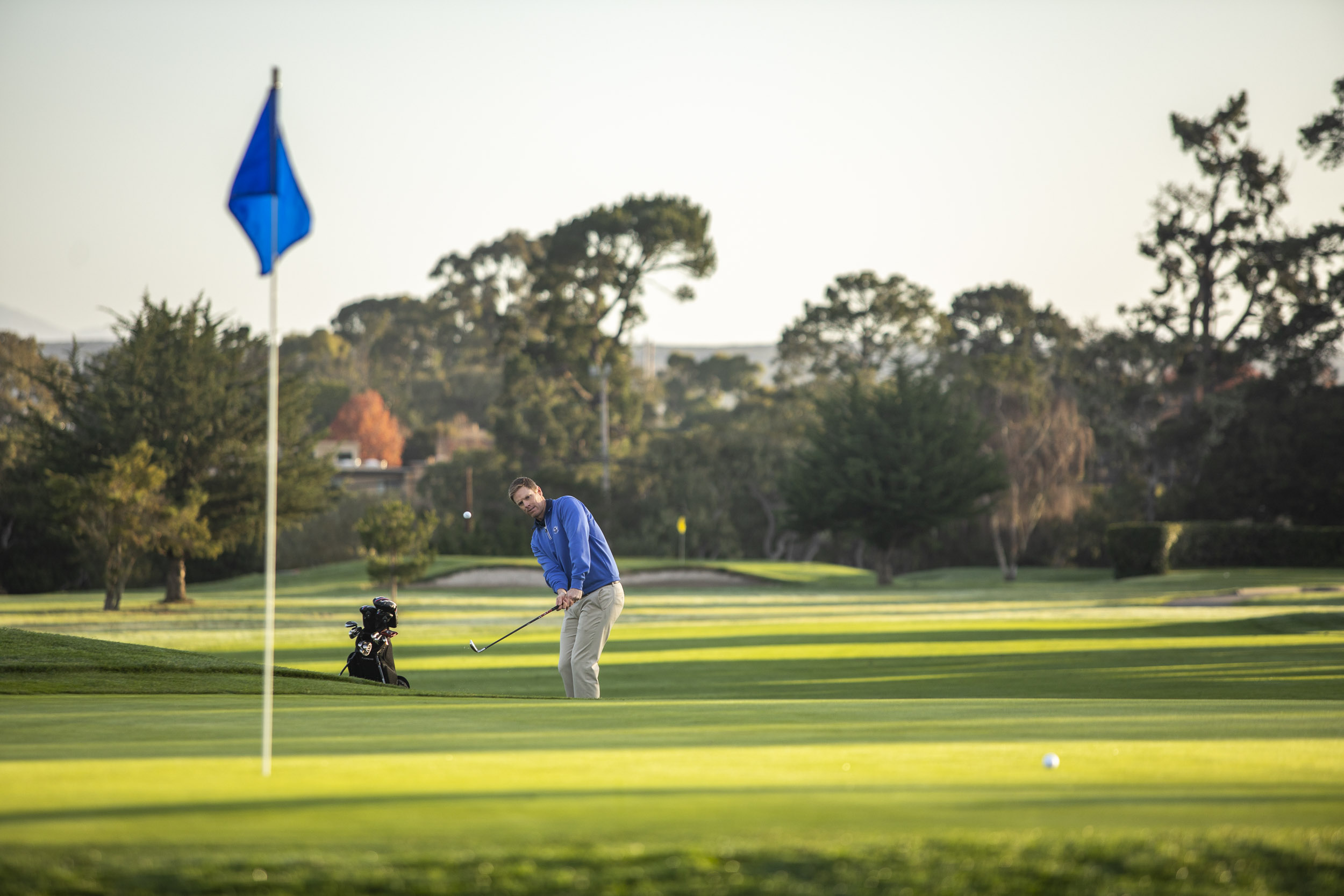 A man makes a chip shot at Del Monte golf Course.