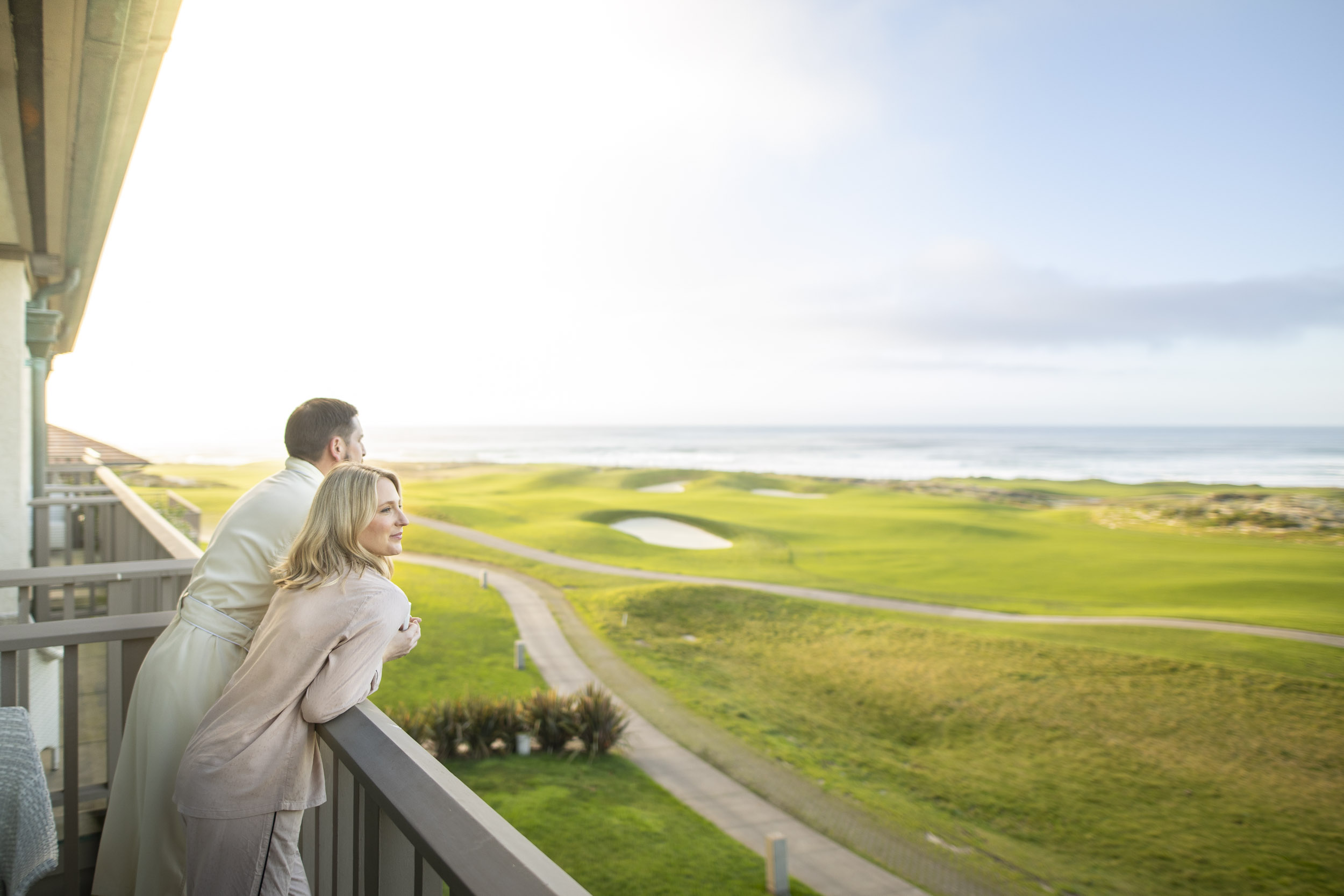 Man and woman enjoy their morning coffee and the ocean view over the Links at Spanish Bay.
